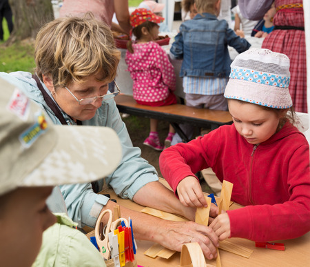 bast basket: ST. PETERSBURG, RUSSIA - JULY 26, 2015: Unidentified girl learns to weave bast basket on a city fair. Master class teaching children folk crafts weaving a basket