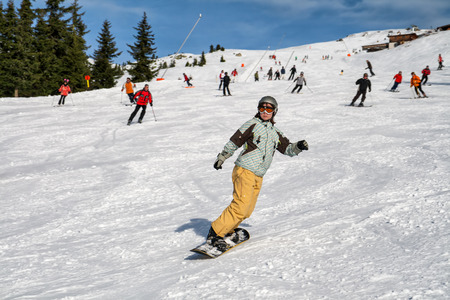slopes: Girl on a snowboard down on the background of a busy ski slope Stock Photo