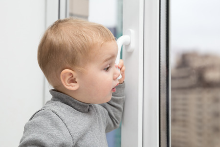 behold: Little baby kid looking out the window Stock Photo