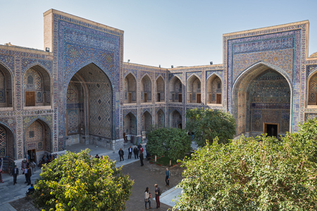 SAMARKAND, UZBEKISTAN - OCTOBER 15, 2016:  People in the courtyard of Ulugh Beg madrasah Editorial