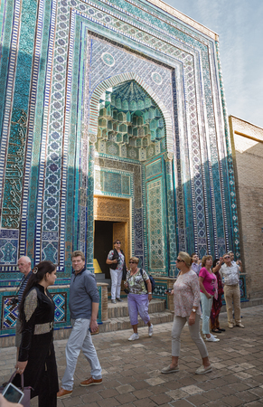 SAMARKAND, UZBEKISTAN - OCTOBER 15, 2016:  People visit the memorial complex Shah-I-Zinda. The upper group of  mausoleums. The Mausoleum of 1361 Stok Fotoğraf - 79119616