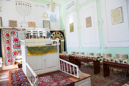 BUKHARA, UZBEKISTAN - OCTOBER 19, 2016: The interior of the very first synagogue in Bukhara. Bima is the platform in the center of the synagogue and a table for public reading of the Torah.  In the frame is the text of the prayer for peace in Hebrew and R Editorial