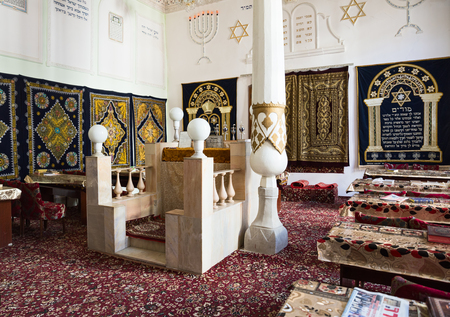 primus: BUKHARA, UZBEKISTAN - OCTOBER 19, 2016: The interior of the very first synagogue in Bukhara, hall of festive worship. Bima is the platform in the center of the synagogue and a table for public reading of the Torah. Editorial
