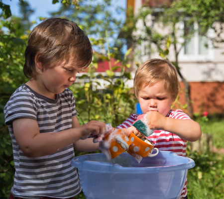Two small boys help to wash dishes outdoors in the village, in the country. Focus on the cup