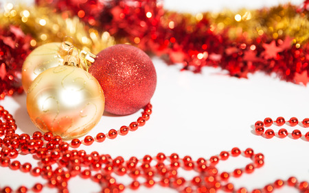 Christmas decorations of red and golden color on a white background - balls, beads and tinsel