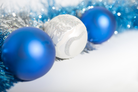 Christmas decorations of blue and silver on a white background - three balls and a tinsel Stock Photo