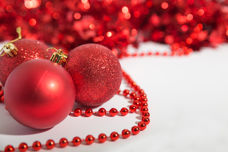 Christmas decorations of red color on a white background - balls, beads, tinsel