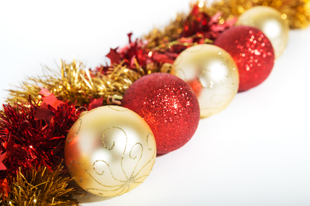 Christmas decorations ofred and golden color on a white background - balls and tinsel Stock Photo