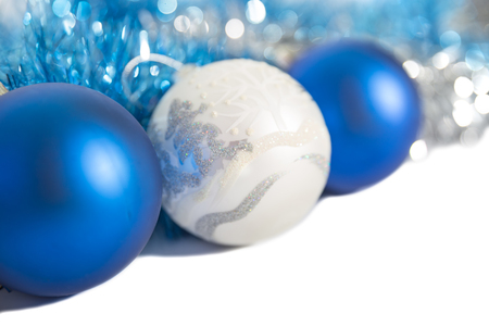Christmas decorations of blue and silver color on a white background - balls and tinsel