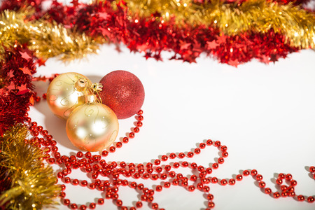 Christmas decorations of red and golden color on a white background - balls, beads,tinsel