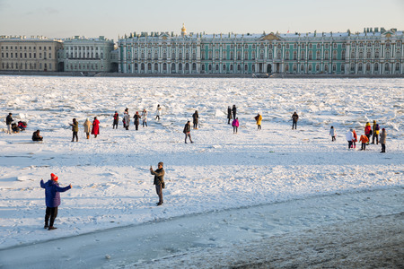 SAINT PETERSBURG, RUSSIA - JANUARY 31, 2018: Neva River was covered with hummocks. People walk on the ice and take a photo on background of ice floes.