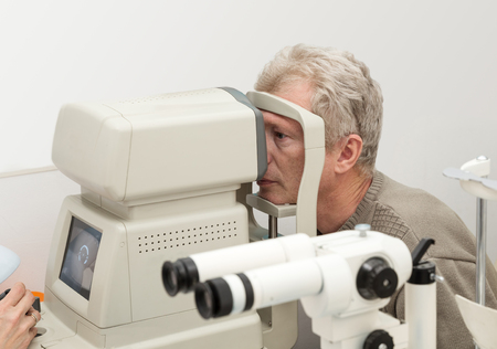 Mature man is checked for vision on diagnostic equipment Фото со стока