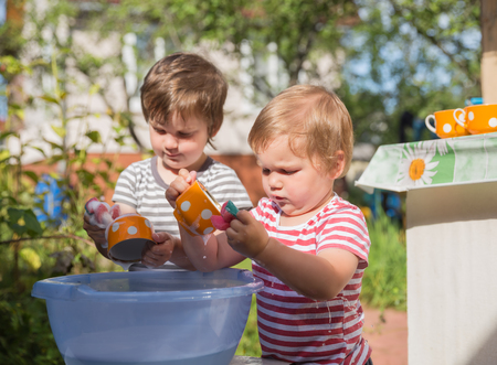 Two small boys washing dishes outdoors in village, in country