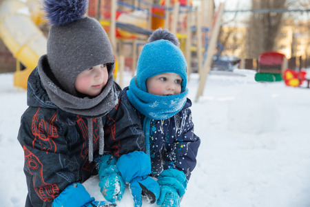 Two cute children boys in warm clothes in winter play in playground