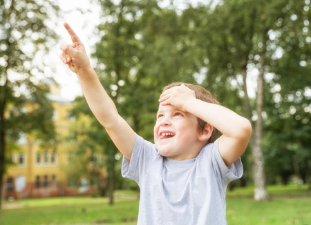Boy 5 years old looks up at something and shows finger in summer park on background of trees Archivio Fotografico