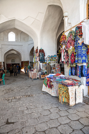 BUKHARA, UZBEKISTAN - OCTOBER 19, 2016: Sale of souvenirs in the trade dome in Bukhara. National clothes, embroidered skullcaps, pillowcases, tablecloths, magnets, paintings and other souvenirs Standard-Bild - 118944918