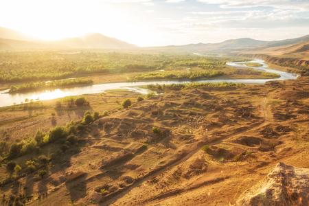 Beautiful landscape in backlit sunlight. Mtkvari River on the background of the Caucasus Mountains, on the banks of the river ruins of a medieval settlement, Uplistsikhe, Georgia