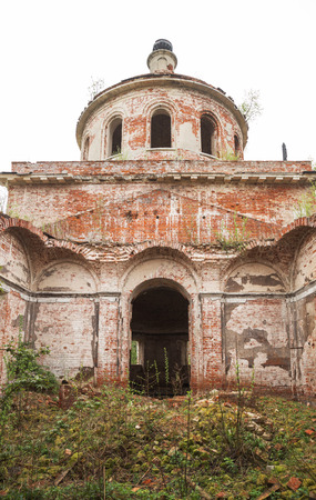 Ruins of old abandoned church. Building with collapsed vault is covered with broken bricks and overgrown grass and bushes. Church of the Nativity of Christ in village Rozhdestvo, Tver region, Russia Banco de Imagens - 124966986