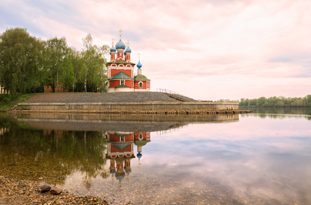 Uglich, Kremlin, Church of Tsarevich Dimitri on blood is reflected in calm water of the Volga River in early morning. Yaroslavl region, Russia