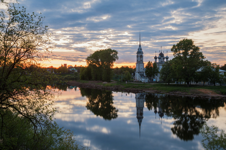 Picturesque cityscape of Vologda, the Church of the Presentation of the Lord, the Candlemas Church, is reflected in water of the river at sunset Фото со стока