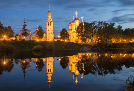 Night view of the illuminated Kremlin with a mirror image in the water of river, Vologda, Russia