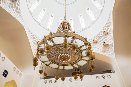 ST. PETERSBURG, RUSSIA - OCTOBER 26, 2019: beautiful chandelier made of glass and metal in interior of the cathedral mosque in Saint Petersburg Editorial