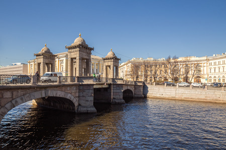 ST. PETERSBURG, RUSSIA - APRIL 18, 2019: Lomonosov bridge over the Fontanka with people and cars and Lomonosov Square. On square is building of the Ministry of Education of Russian Empire, 1828