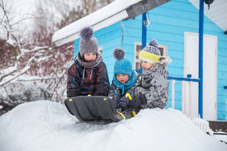 Happy children sledding in winter in yard. Three little kids in warm overalls play outside on frosty winter day. Three brothers sledding from small snow slide 写真素材
