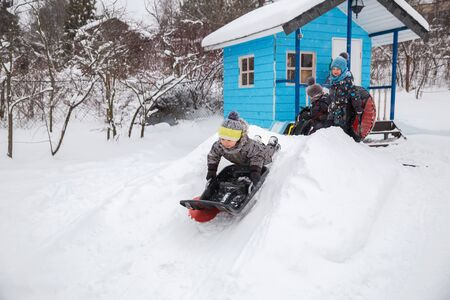 Children sledding in winter in yard. Three little kids in warm overalls play outside on frosty winter day. Three brothers take sleigh ride in turn from small snow slide 写真素材