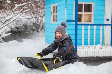 Little boy sledding in winter in yard. Child enjoys winter fun. Children ride a sleigh with snow slide 写真素材