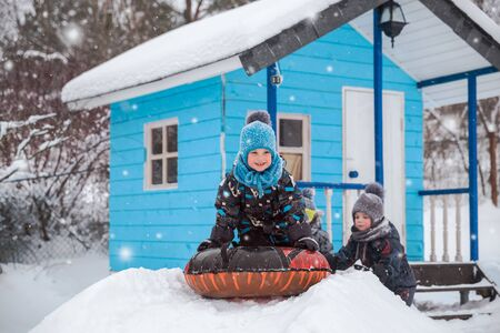 Happy children sledding in winter in yard. Three little kids in warm overalls play outside on frosty winter day. Three brothers take sled ride in turn from small snow slide on inflatable sled