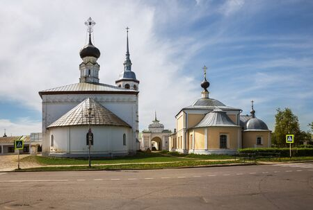 Suzdal, Golden Ring of Russia. Architectural ensemble of two Churches Resurrection of Christ (Voskresenskaya) and Kazan Icon of Mother of God (Kazanskaya) on Market Square. In background gates of Gostiny Dvor (shopping arcade) 写真素材 - 136790000