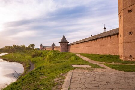 Fortress wall with towers of Euthymius Monastery on  banks of the Kamenka River on summer evening. Suzdal, Golden Ring of Russia