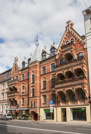 RIGA, LATVIA - SEPTEMBER 01, 2014: Riga Art Nouveau (Jugendstil), red brick house with large balconies and weather vane on tower in the central area of city