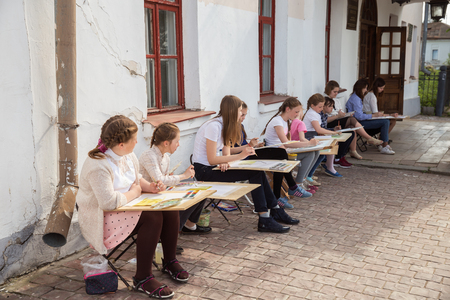 SUZDAL, RUSSIA - MAY 15, 2018: Children teenagers paint in the open air. Lesson of drawing from nature. Schoolchildren learn to paint with watercolors on a city street 報道画像