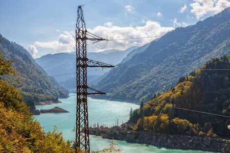 High voltage tower in mountains of Caucasus. Hydropower, transmission line pylon on background of  reservoir of Enguri hydroelectric station (Enguri HES). Mountain landscape. Georgia, Svaneti Standard-Bild