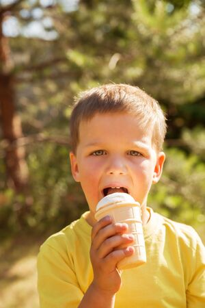 Boy 4 years in yellow t-shirt in summer outdoors on hot sunny day. Child eats ice cream in waffle cup Imagens
