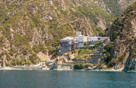 Holy Mount Athos in Greece. Monastery of St. Dionysiou on background of steep mountain slopes