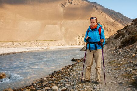 Trekking in the Himalayas. Tired young woman on trail along banks of the Kali Gandaki River, Lower Mustang, Nepal.