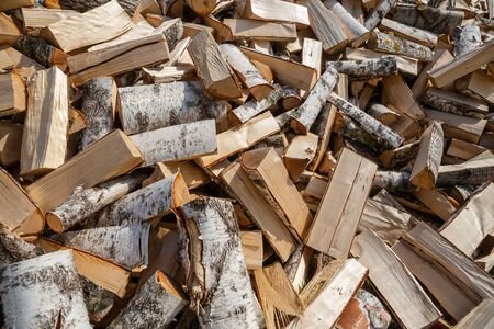 Large pile of chopped birch firewood. Stock of firewood for the winter