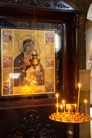 TBILISI, GEORGIA - SEPTEMBER 23, 2018: Wax candles burn in a candlestick in front of the Orthodox icon of the Mother of God in Sioni Cathedral