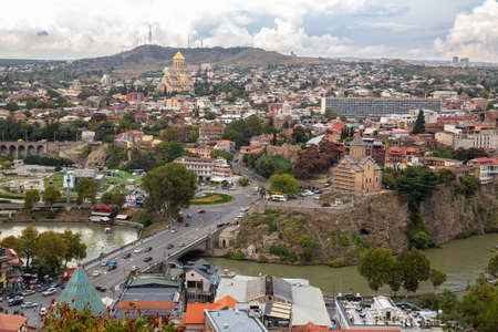 TBILISI, GEORGIA - SEPTEMBER 23, 2018: Aerial panoramic view of the old city of Tbilisi. The old Metekhi church and the new Trinity Cathedral