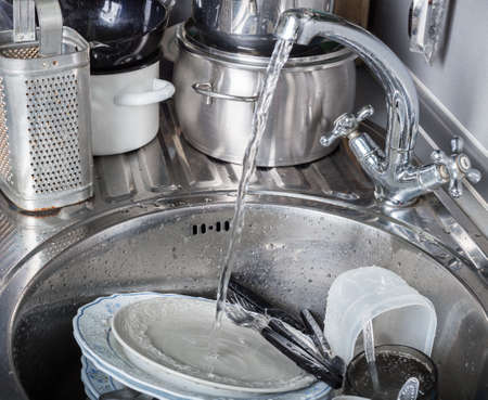 Jet of water pours from the tap onto dirty dishes in kitchen sink