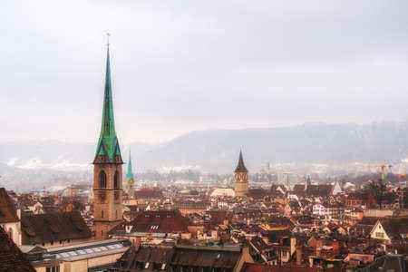 View of Zurich on a foggy winter day. Gothic spiers of churches in the background of the Alps ridge 免版税图像
