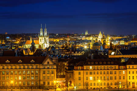 Night Prague. View of the old town and illuminated landmarks above the rooftops