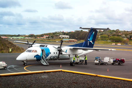 TERCEIRA, AZORES, PORTUGAL - MAY, 2012: Small turboprop aircraft Bombardier Q200 of airline SATA Air Açores flies between islands of Azores archipelago. Loading luggage at Terceira Island airport