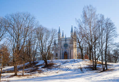 PETERHOF, SAINT PETERSBURG, RUSSIA - MARCH, 2021: Early spring in Alexandria park, Gothic chapel on a hillock 新闻类图片