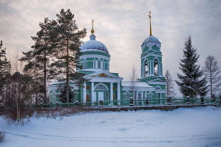 Rural Church of St. Apostles Peter and Paul on a winter evening. Somino, Leningrad region, Russia 免版税图像