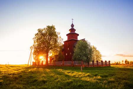 Old rural wooden church of St. John the Theologian on the Ishnya River. Spring sunset landscape. Yaroslavl region, Golden ring of Russia. 免版税图像