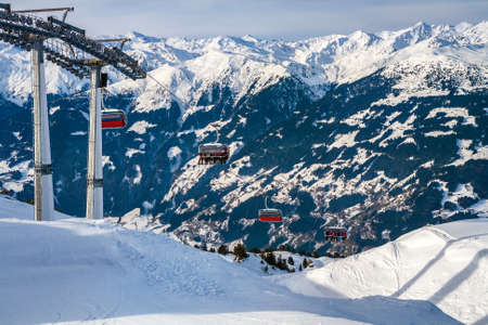 Chairlift in the Alps against the backdrop of mountain peaks. Skiers and snowboarders climb the slope on the cable car. Ski resort in Austria, Zillertal Arena 免版税图像